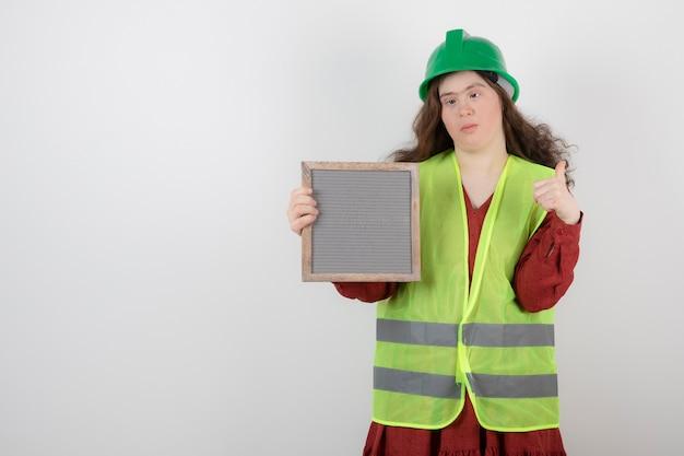 Schattig meisje met het syndroom van down permanent in vest en met een frame.