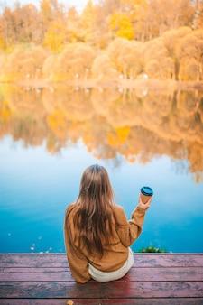 Schattig meisje met warme afhaalkoffie buiten op herfstdag in de buurt van meer