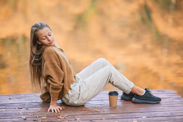 Schattig meisje met warme afhaalmaaltijden koffie buiten op herfstdag in de buurt van meer