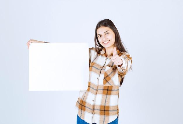 Schattig meisje met witte grote blanco duimen opgevend. Gratis Foto