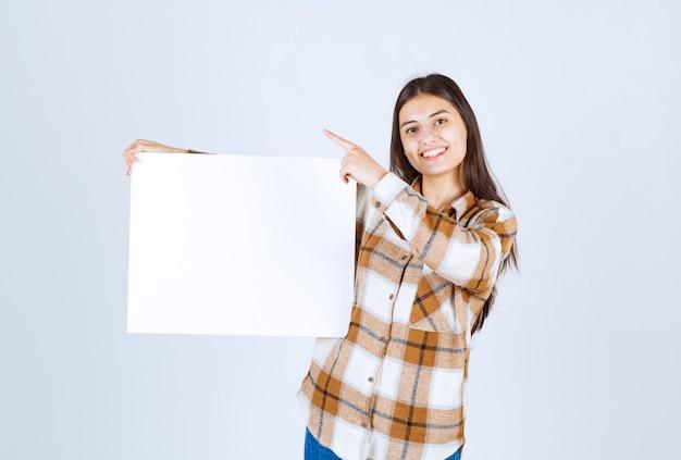 Schattig meisje met witte grote lege kaart op witte muur.