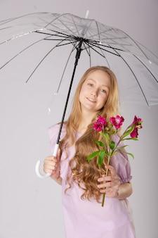 Schattig meisje onder een paraplu met bloemen