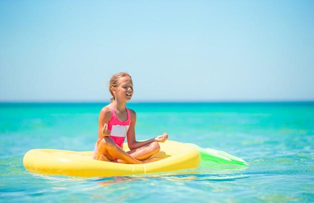 Schattig meisje ontspannen op opblaasbare luchtbed in de zee