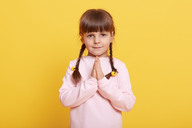 Schattig meisje op haar handpalmen te drukken, kind maken wens, poseren geïsoleerd op gele achtergrond, vrouwelijk kind uiting van verlangen, geloof, god vragen om te helpen, oprechte wens, klein meisje met staartjes bidden.