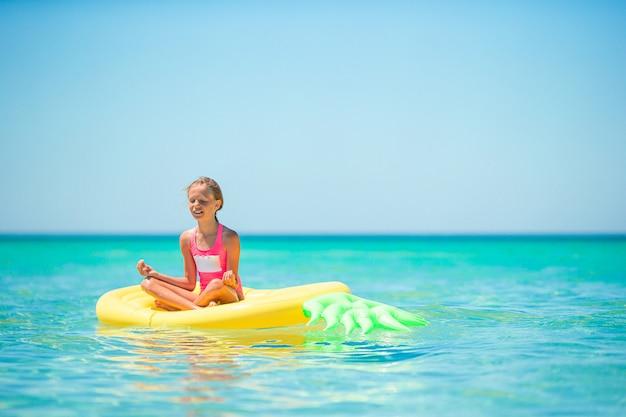Schattig meisje op opblaasbare luchtbed in de heldere zee