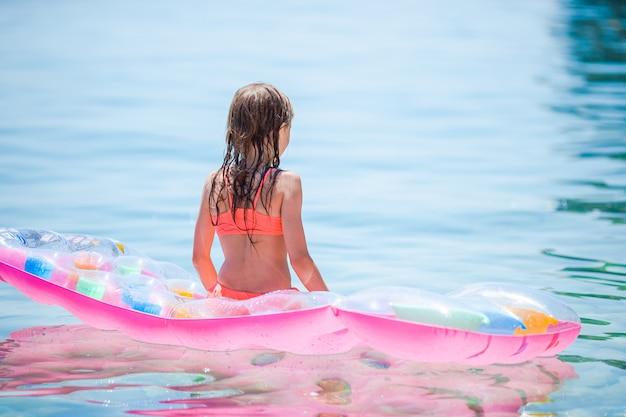 Schattig meisje op opblaasbare luchtbed in de zee