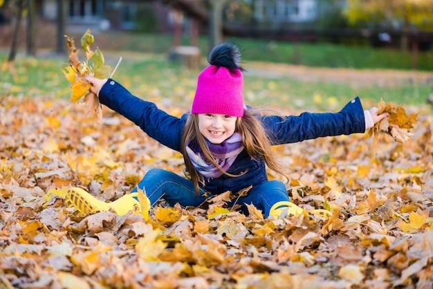 Schattig meisje plezier op herfstdag. gelukkig kind gooien herfstbladeren en glimlachen buitenshuis.