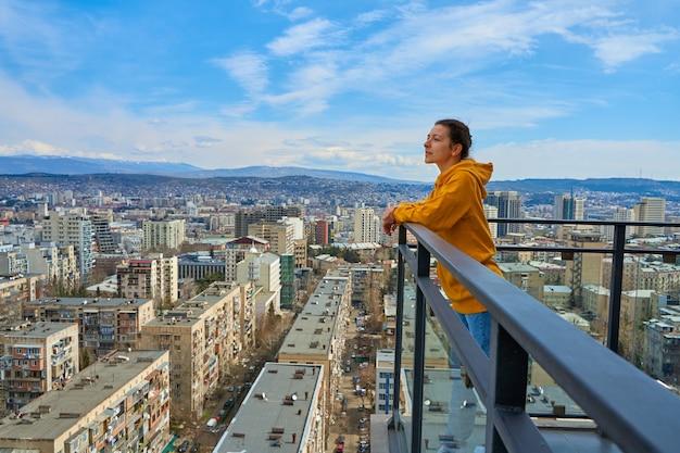 Schattig meisje poseren terwijl ze op het balkon van de wolkenkrabber staat of