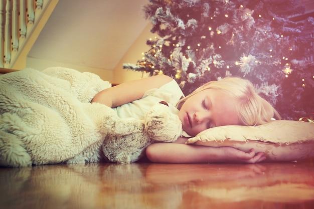 Schattig meisje slaapt op de vloer onder de kerstboom