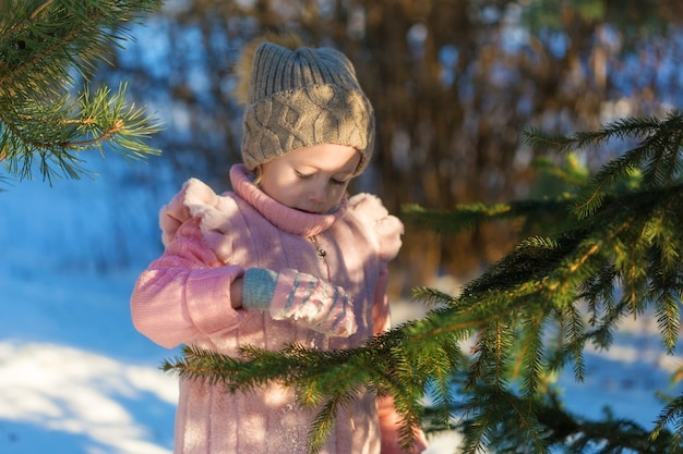 Schattig meisje speelt met dennenboom in winter forest. gelukkige jeugd. kids outdoors.winter fun holiday concept