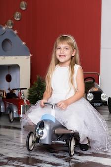 Schattig meisje speelt met speelgoedauto's. rijdt op een speelgoedmachine met typemachine. gelukkige jeugd