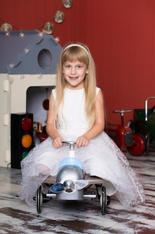 Schattig meisje speelt met speelgoedauto's. rijdt op een speelgoedmachine met typemachine.