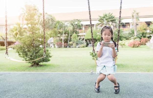 Schattig meisje student spelen slimme telefoon op schommel