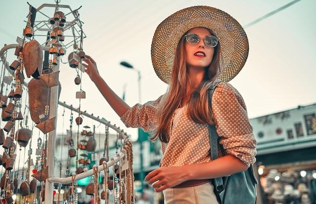 Schattig meisje toerist in een blouse, een strooien hoed en zonnebril met een rugzak loopt door de straten van de stad en kiest sieraden op de markt. reizen, toerisme concept.