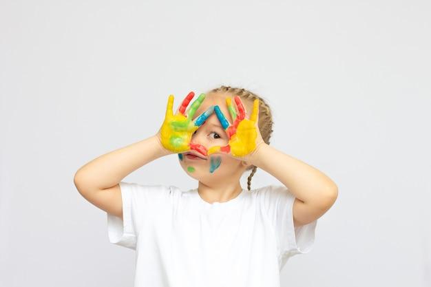 Schattig meisje toont haar handen geschilderd in felle kleuren, geïsoleerd over white