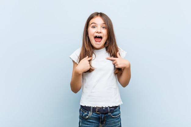 Schattig meisje verrast wijzend op zichzelf, breed glimlachend