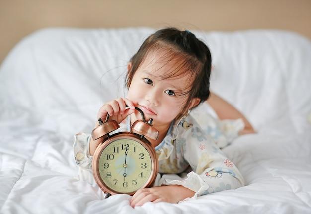 Schattig meisje wordt wakker in de ochtend met wekker op bed