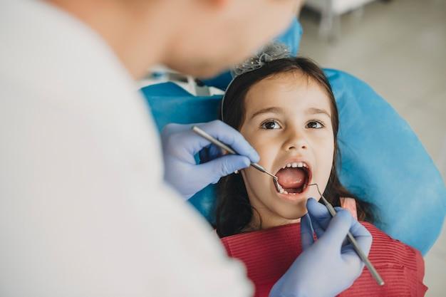 Schattig meisje zittend in een stoel stomatologie met mond geopend tijdens een tandoperatie door een pediatrische tandarts.