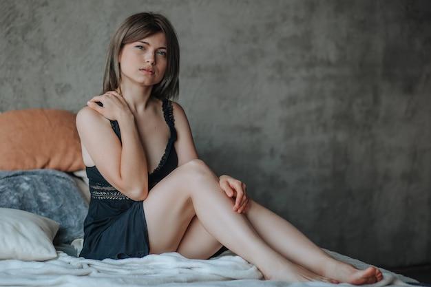 Schattig meisje zittend op bed in de ochtend in zwarte lingerie