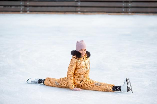 Schattig meisje zittend op ijs met schaatsen na de herfst