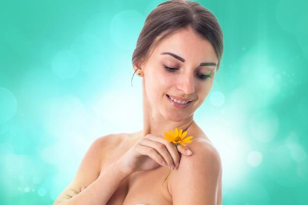 Schattig meisje zorgt voor haar huid met gele bloem in handen geïsoleerd op een witte achtergrond. gezondheidszorgconcept. lichaamsverzorgingsconcept. jonge vrouw met een gezonde huid.