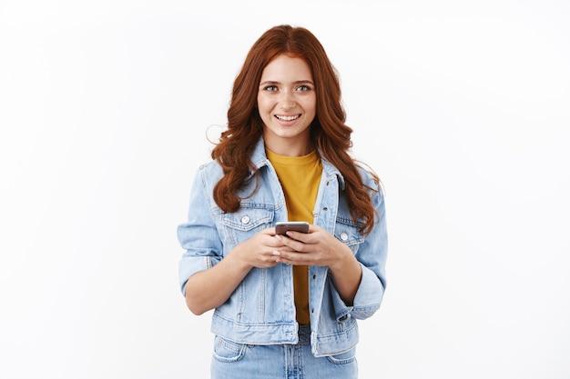 Schattig modern jong roodharig meisje met sproeten in spijkerjasje, smartphone vasthouden en opgetogen glimlachen, smm freelancer werkt op afstand, neem contact op met klanten via mobiele telefoon, witte muur