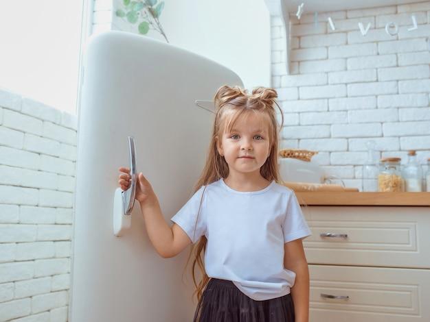 Schattig mooi klein kaukasisch meisje met lang haar in witte t-shirt koken in de keuken
