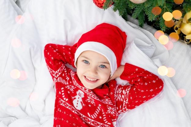 Schattig mooi meisje kind bij de kerstboom in een rode trui en hoed op oudejaarsavond of kerstmis thuis op een wit bed wachten op een vakantie en geschenken