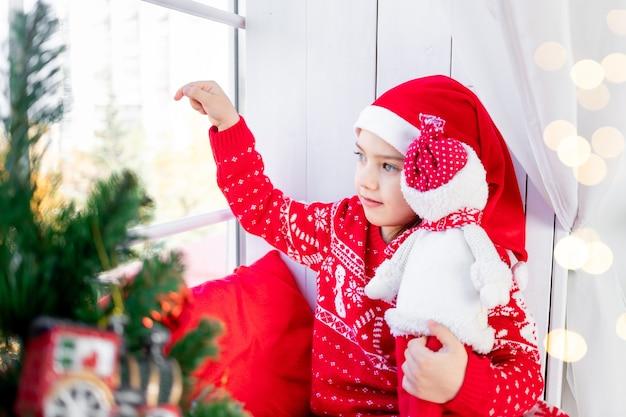 Schattig mooi meisje kind op het raam met een kerstboom in een rode trui en hoed op oudejaarsavond of kerstmis thuis en wachten op een vakantie en geschenken