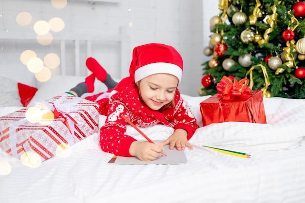 Schattig mooi meisje kind schrijft een brief aan de kerstman bij de kerstboom in een rode trui en hoed op oudejaarsavond of kerstmis thuis op een wit bed