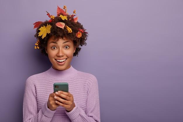 Schattig mooi meisje met donkere huid houdt moderne mobiele telefoon vast, kijkt rechtstreeks naar de camera, gaat telefoneren, glimlacht gelukkig, gekleed in een casual outfit, poseert tijdens de herfst, geïsoleerd op paarse muur