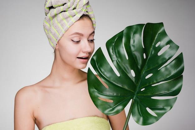 Schattig mooi meisje met een handdoek op haar hoofd houdt een groen blad vast, geniet van een spa