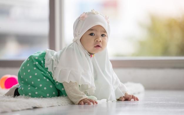 Schattig moslim babymeisje liggend op de vloer camera kijken.