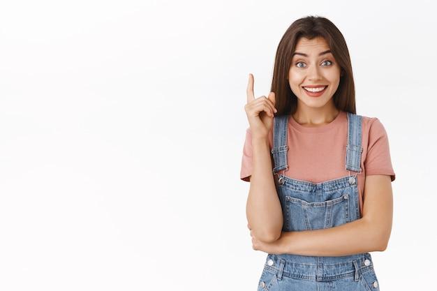 Schattig opgelucht meisje kreeg eindelijk een uitstekend idee, deelde haar plan of suggestie, glimlachte blij en dwaas uitziende camera, stak een vinger op in eureka-gebaar, kreeg oplossing, staande witte achtergrond