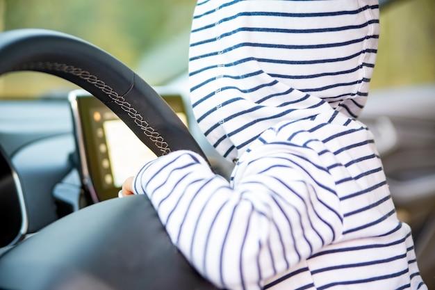 Schattig peutermeisje dat een moderne auto bestuurt.