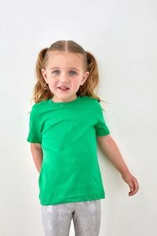 Schattig peutermeisje met paardenstaarten gekleed in een heldergroen t-shirt dat naar de camera kijkt en lacht tegen een witte achtergrond