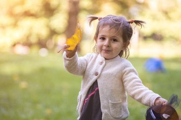 Schattig peutermeisje steekt een herfst geel esdoornblad in de camera..
