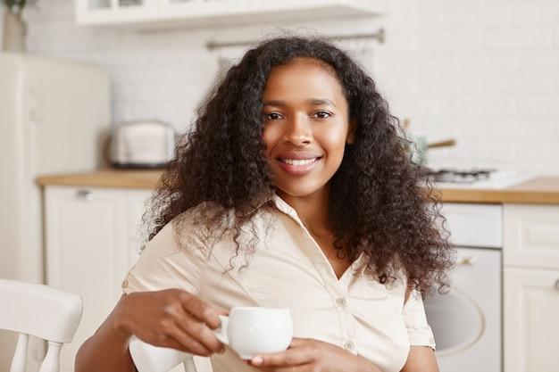 Schattig positief twintig-jarige mulat meisje met volumineuze afro kapsel met vrolijke gelukkige gezichtsuitdrukking, genieten van mooie ochtend thuis, zittend in de keuken, breed glimlachend