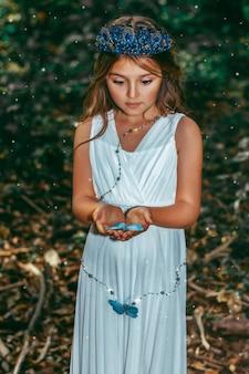 Schattig prinsesje meisje met blauwe vlinders in het bos. kunst verwerking.