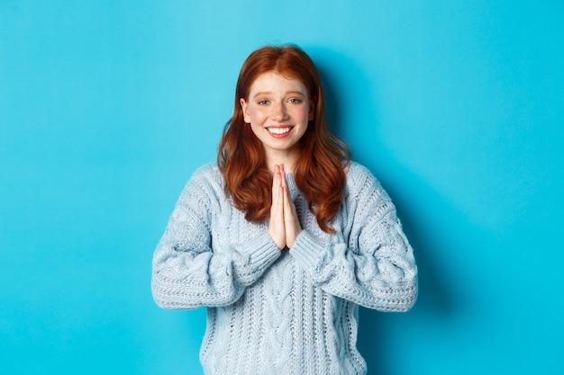 Schattig roodharig meisje dat bedankt zegt, glimlacht en naar de camera kijkt, dankbaarheid uitdrukt, staande tegen een blauwe achtergrond.
