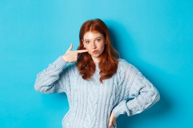 Schattig roodharig meisje in trui die haar wang prikt, brutaal naar de camera staart, staande over blauwe achtergrond