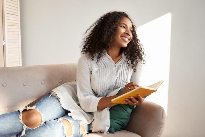 Schattig schattig afro-amerikaanse student meisje met zwart volumineus haar genieten van vrije tijd na de universiteit, liggend op de bank in stijlvolle gescheurde spijkerbroek en blouse, gedachten en ideeën delen in haar dagboek