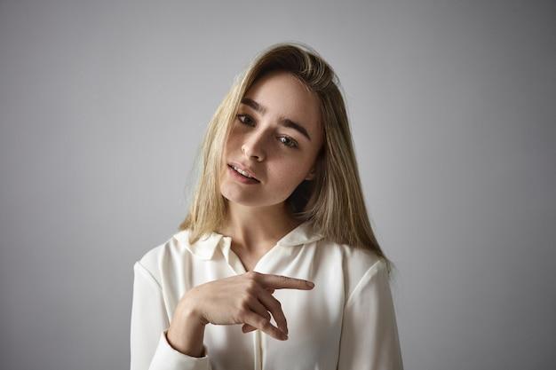 Schattig schattig blond meisje in witte blouse poseren geïsoleerd in studio, glimlachend in de camera. mooie stijlvolle jonge vrouw, gekleed in zijdeachtig elegant shirt, kantelend hoofd, wijsvinger zijwaarts wijzend