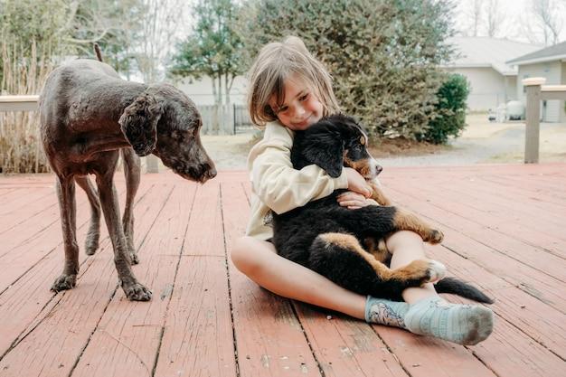 Schattig schattig kindmeisje zit met gedomesticeerde honden en knuffelt kleine berner puppy op de veranda