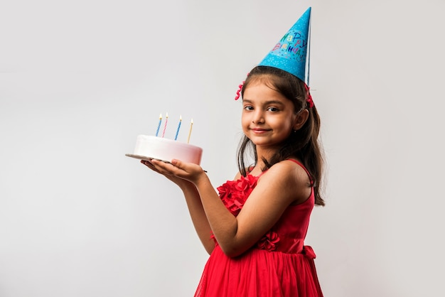 Schattig schattig klein indiaas of aziatisch klein meisje dat verjaardag viert terwijl ze aardbeientaart vasthoudt en kaarsen blaast aan tafel of geïsoleerd staat op witte of rode achtergrond