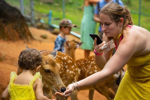 Schattig schattig peutermeisje met moeder die kleine herten voedt op een kinderboerderij, mooi babykind