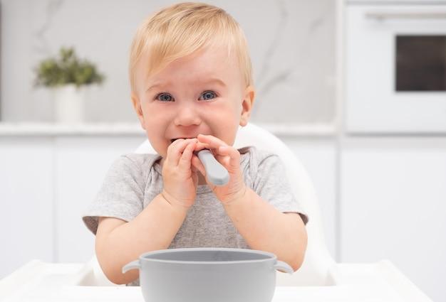 Schattig schattig triest blanke blonde babymeisje huilend eten van siliconen plaat op kinderstoel in de keuken, met lepel in de mond, camera kijken. gezonde voeding voor kind concept.