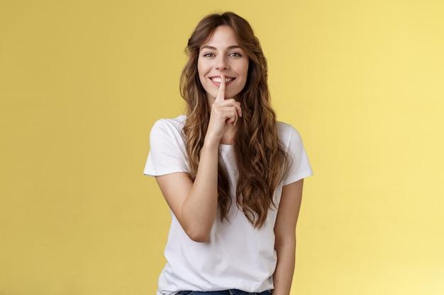 Schattig sluw mooi europees meisje krullend kapsel verbergen schoonheid geheim glimlachend sensueel tonen hush shush gebaar wijsvinger ingedrukt lippen grijnzend vrolijk staan gele achtergrond.
