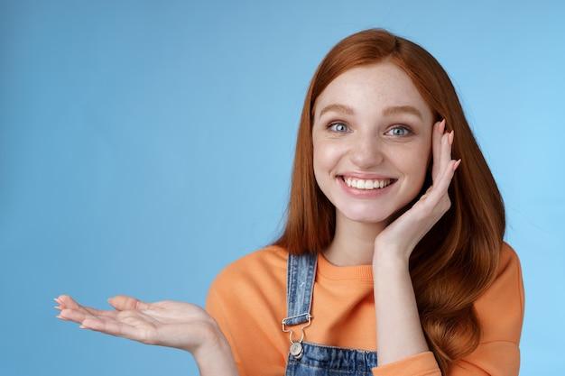 Schattig teder chatismatisch blij lachend roodharige meisje presenteert geweldig product show object palm vasthouden hand omhoog lege kopie ruimte grijnzend onder de indruk ontvangen dwaas charmant cadeau blauwe achtergrond