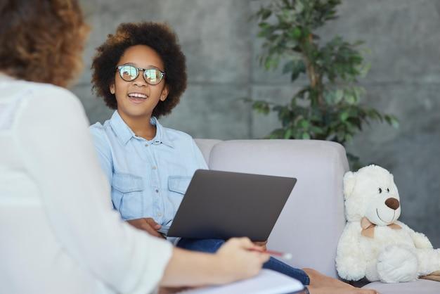 Schattig tienermeisje glimlachend luisterend naar haar vrouwelijke leraar die laptop gebruikt om te studeren terwijl ze een